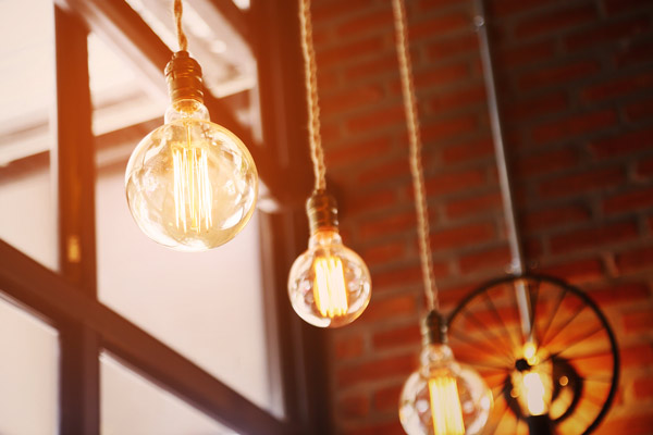 Inspire with your ideas and energy. Image of lit Edison-style lightbulbs